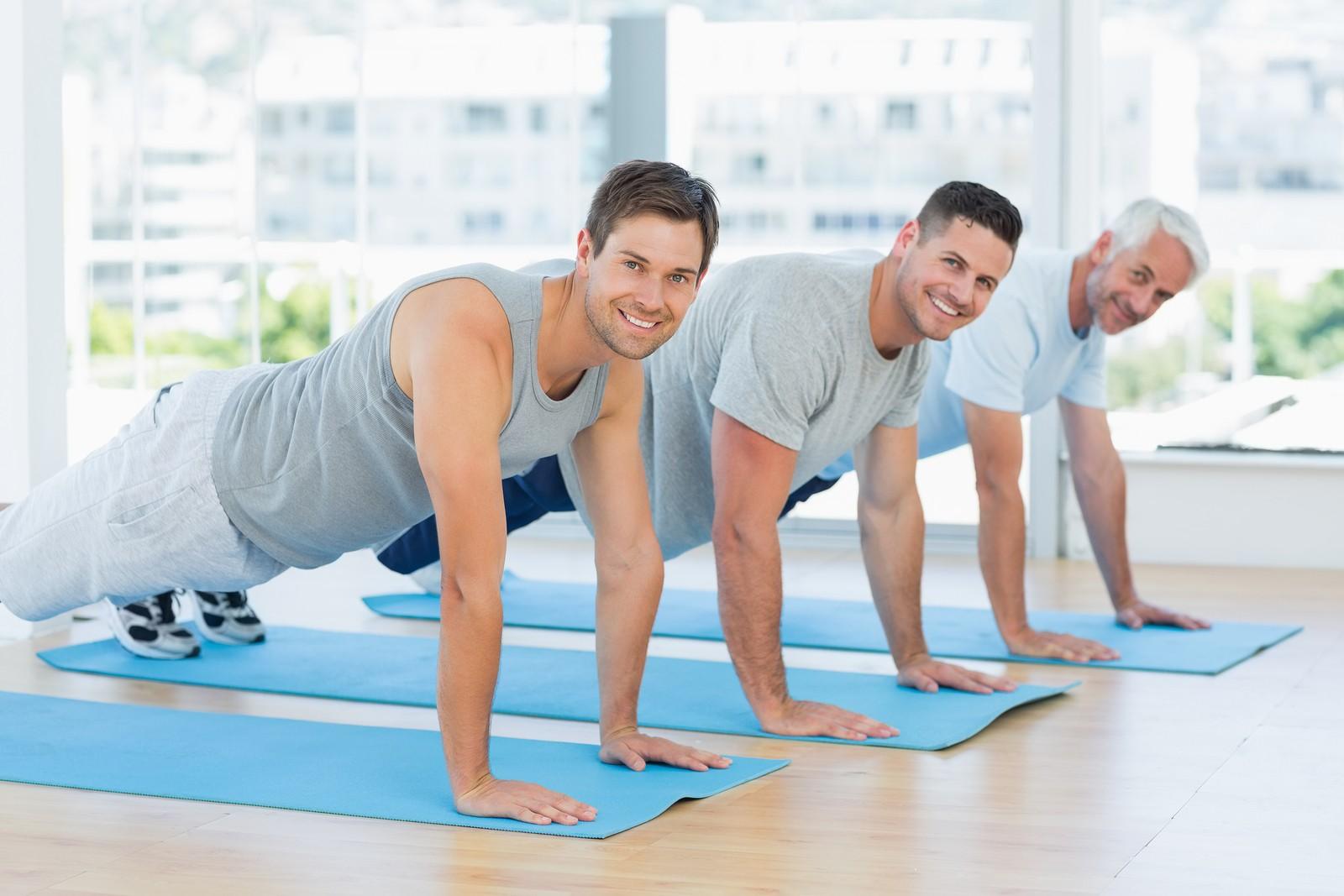 Portrait of happy fit men doing push ups at gym